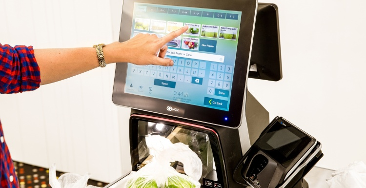 Photo: Person operating a self-checkout terminal; copyright: NCR GmbH...