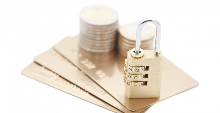 Credit cards and coins with a combination lock; copyright: panthermedia.net /...