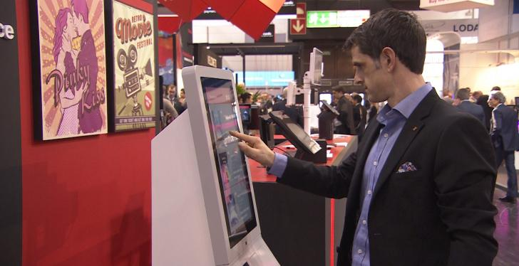 Man uses self service kiosk with touch screen; copyright: beta-web...