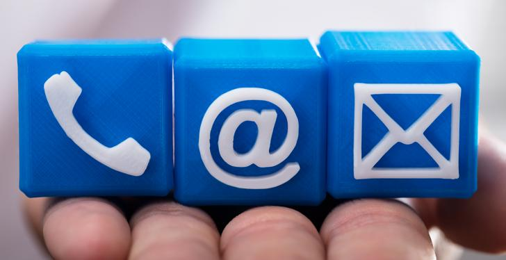 Hand holding little blue blocks with phone, mail and at-icon; copyright:...