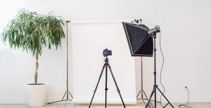 Camera tripod pointing at a white wall.