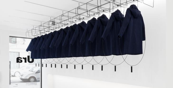 Installation in an empty white store with rain coats hanging from the ceiling;...