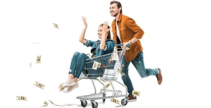 Woman sitting in a shopping cart driven by a man, throwing bank notes away;...