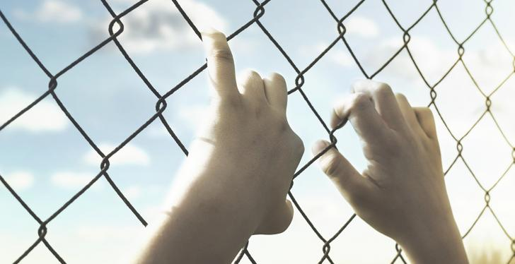 Hands holding onto a wire mesh fence, sunshine behind the fence; copyright:...