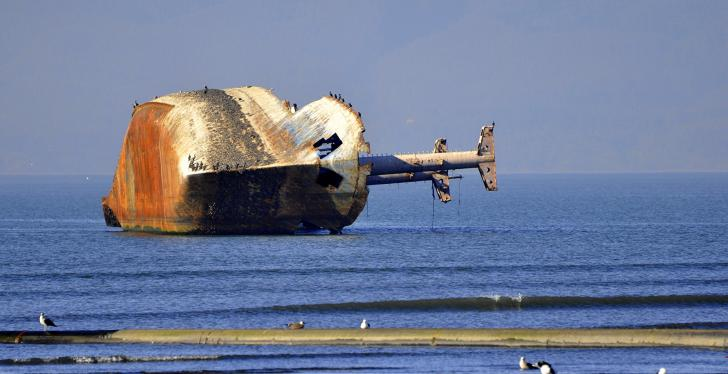 Wrecked ship lying on its side in the sea close to the shore; copyright:...