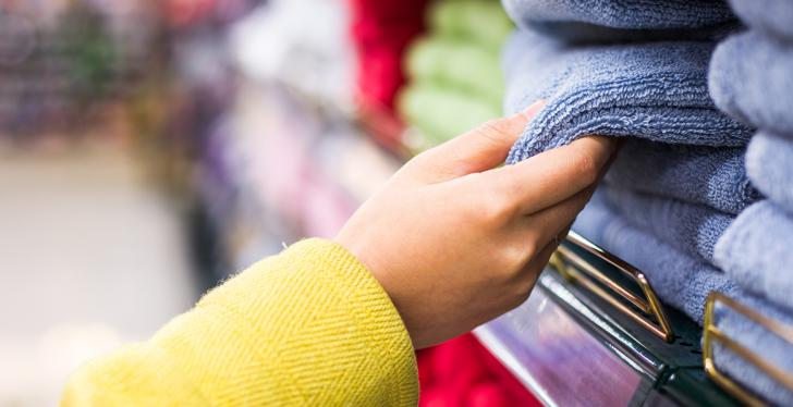 Hand taking a towel out of a stack of towels in a store; copyright:...