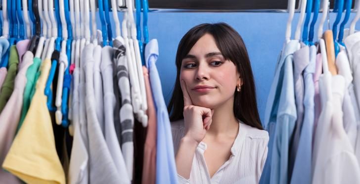 Woman looks through clothes on clothes racks; copyright:...