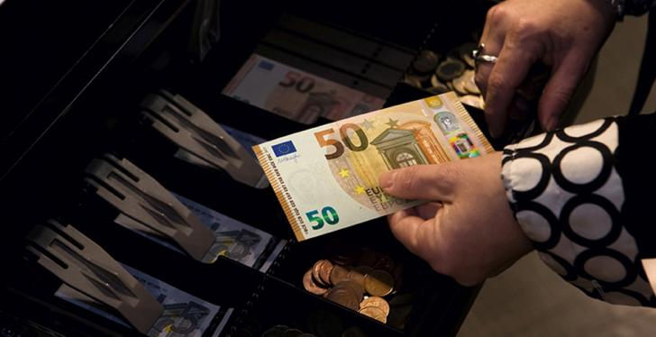 Cash register, woman holding 50 Euro note in her hands...