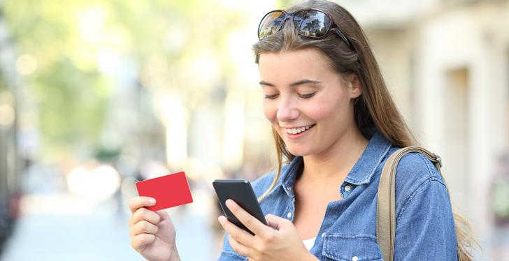young woman looking at her smartphone while holding a gift card in her hand...