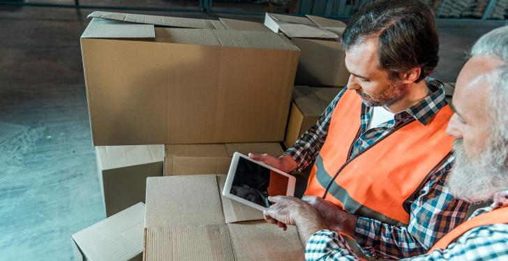 Two men working in logistics using a tablet
