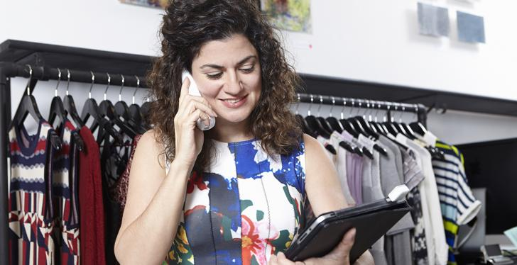 A saleswoman looks at her tablet while shes on a smartphone call....