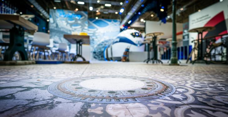 A printed floor in an exhibition hall with the visual of a manhole cover...