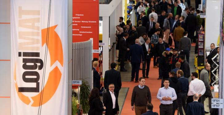Visitors in an exhibition hall; on the left a logo from the LogiMAT exhibition...