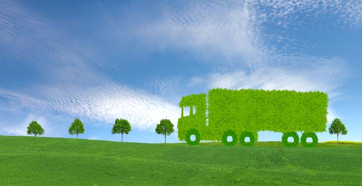 A truck made of grass driving through a green landscape...
