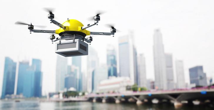 A delivery drone over water in front of skyscrapers...