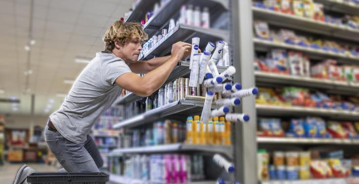 Man crouching in front of a shelf from which deodorant bottles fall...