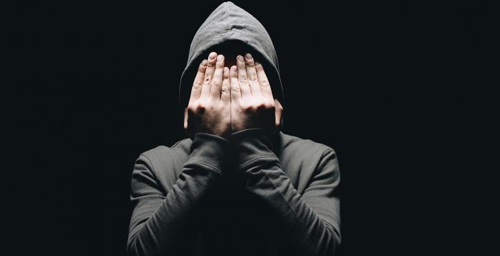 A person in a hoodie puts his hands in front of his face...