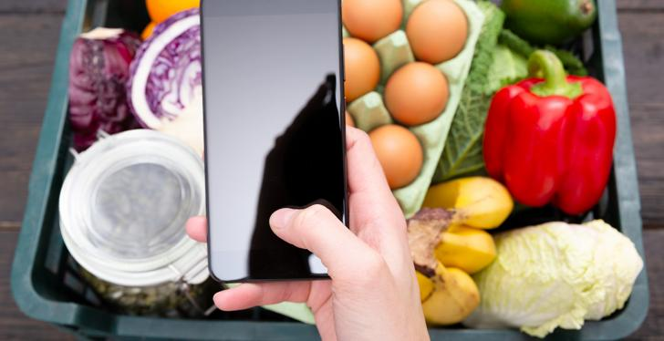A hand holds a smartphone and behind it is a basket of fresh food...