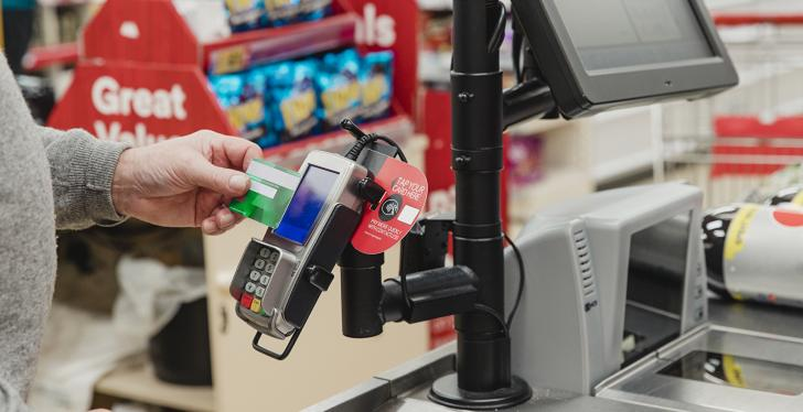 A man pays contactlessly at the supermarket checkout...