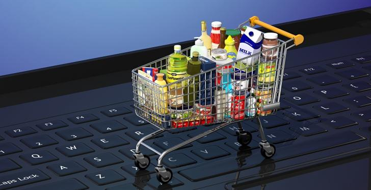 A full mini shopping cart is on the keyboard of a laptop...