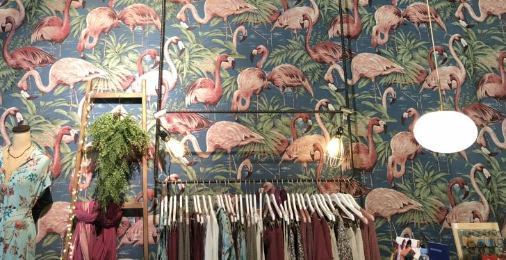 A wallpaper with flamingos, in front: a wardrobe with clothes...