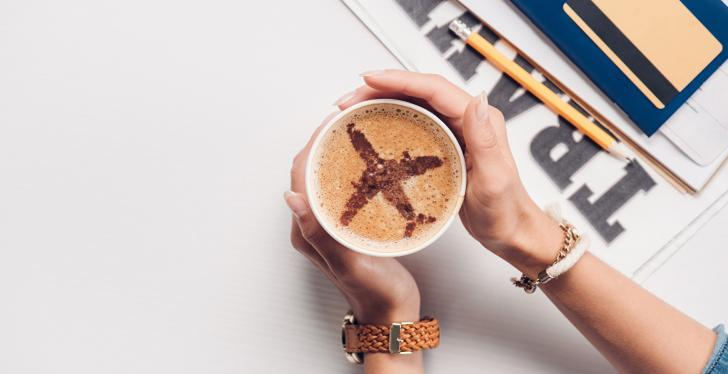 Woman holding a cup of capuccino with an airplane drawn in...