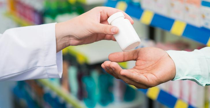 Pharmacist hands a small package of pills to someone...