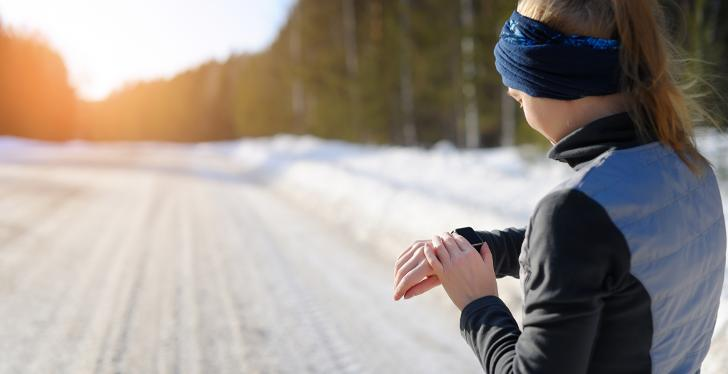 A woman in sportswear stands on a snow covered road and looks at her Smart Watch...