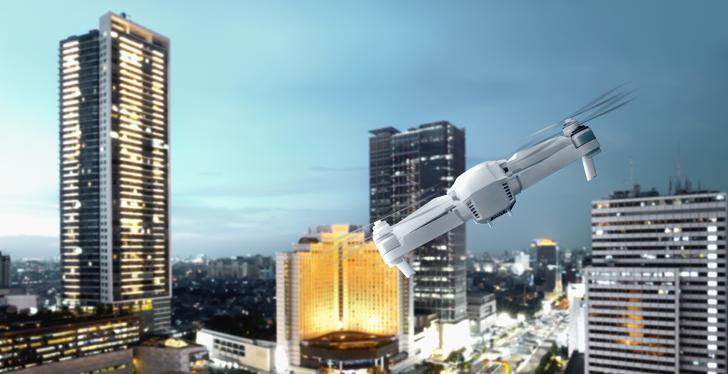A white drone flying high in a city with skyscrapers...