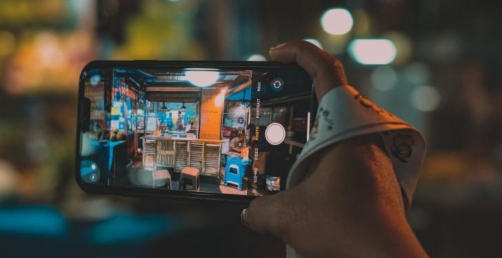 One hand is holding a smartphone with camera function that films a store...
