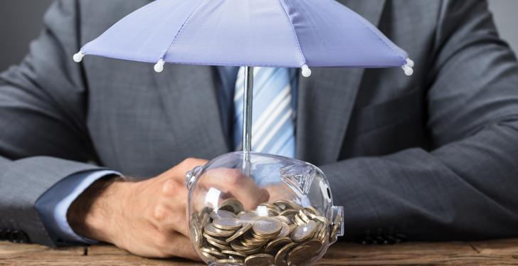 A business man sitting behind a piggybank with a small umbrella over it...