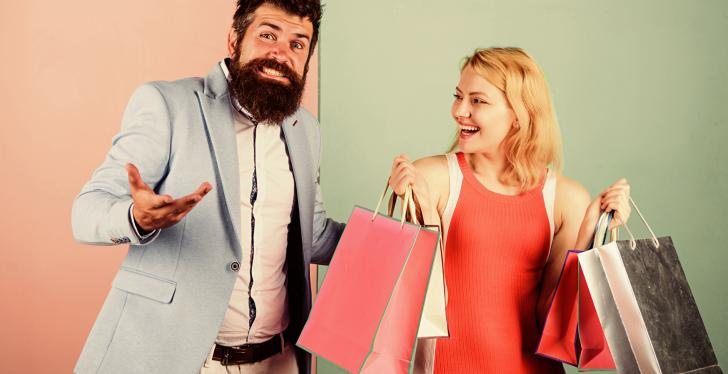 A man and a woman laughing with shopping bags