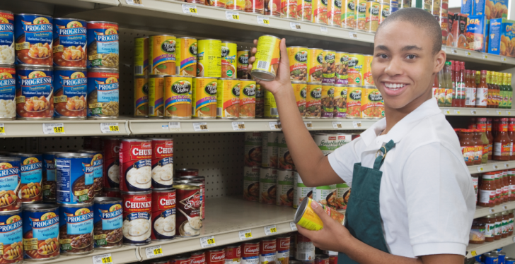 A young man in an apron puts goods on a supermarket shelf; copyright: POS Tuning...