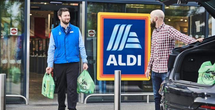 An Aldi employee carries a customers purchase to his car...
