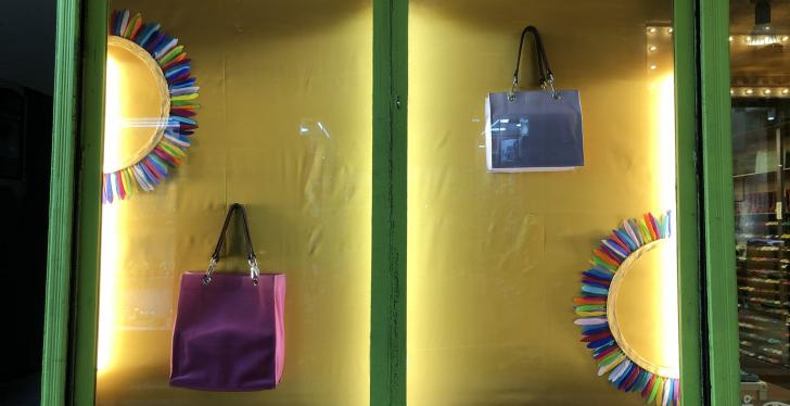 An illuminated shop window with a yellow background and two handbags and...