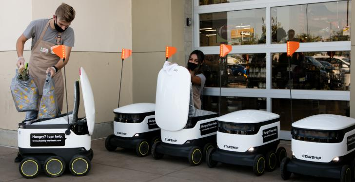 A man is putting shopping bags into a delivery robot and his colleague is...