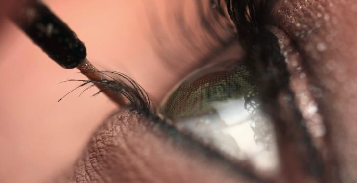 Close up of a woman's eye applying make-up