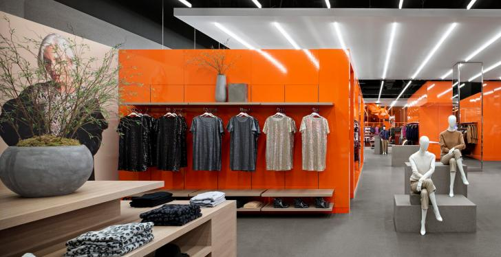 Interior of a flagship fashion store with bright orange furniture and grey...