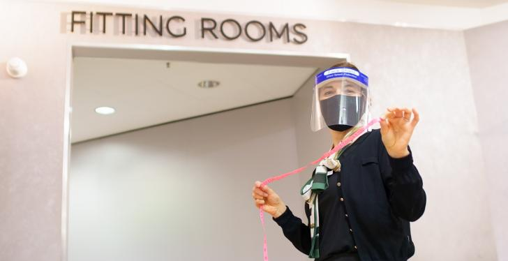 A woman with face mask and measuring tape in front of a fitting room...