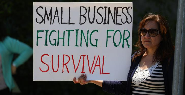 "A woman holding a sign that says ""small businesses fighting for survival"";..."