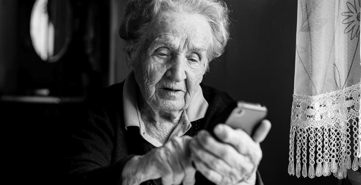 A senior woman uses a smartphone, image in black and white; copyright:...