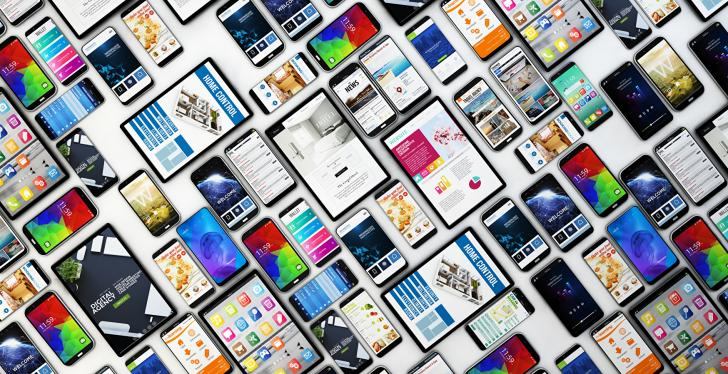 Many smartphones and tablet PCs lying on the ground in a grid pattern;...