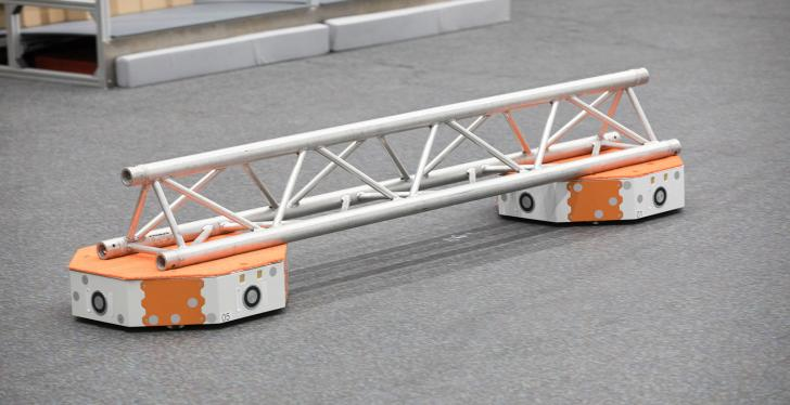 Autonomous transport vehicle transports a steel beam...