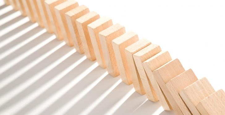 A falling row of wooden dominoes on a white background; copyright:...