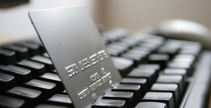 A silver credit card is standing between the buttons of a laptop keyboard...