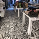 A tiled floor with black and white patterns in a shop...