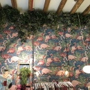 A clothing store with a wallpaper with flamingos and hanging ivy on the ceiling...