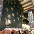 A clothing store with ivy hanging from the ceiling