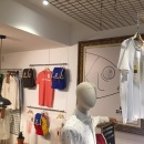 A black grille attached to the ceiling in a clothing store, from which a shirt...