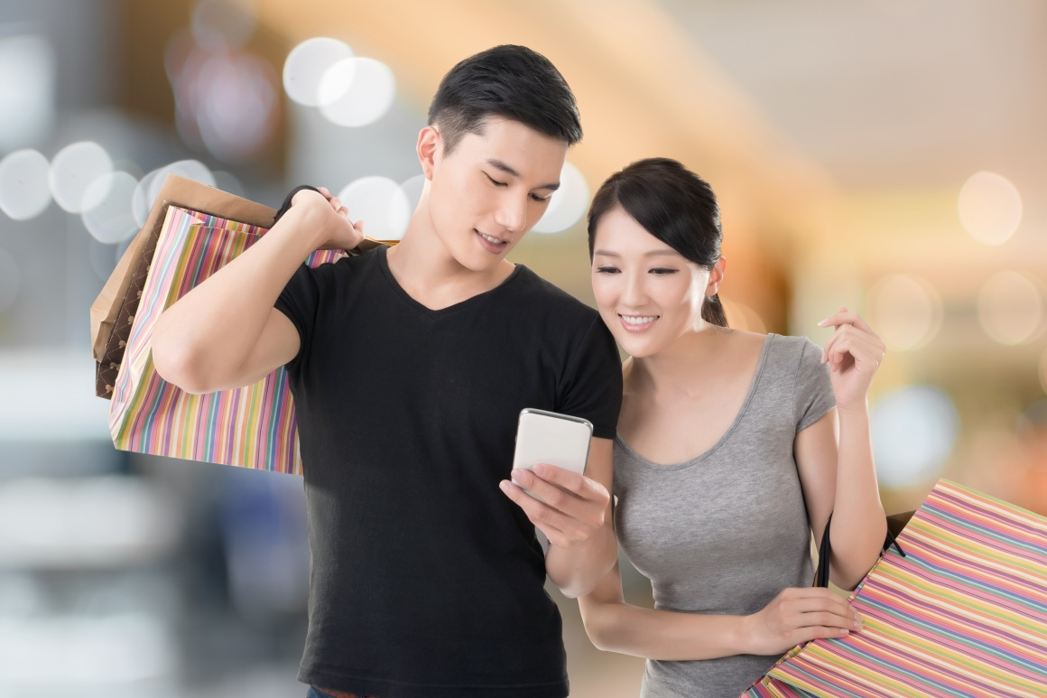 Photo: Shopping couple looking at a smartphone; copyright: panthermedia.net /...
